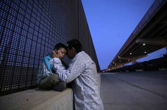 Jose Beltran hugs his son as he sits on the concrete footing to the border fence, the United States only feet away after his long journey from Guatemala. Jose surrendered to Border Patrol and his asylum case begins.