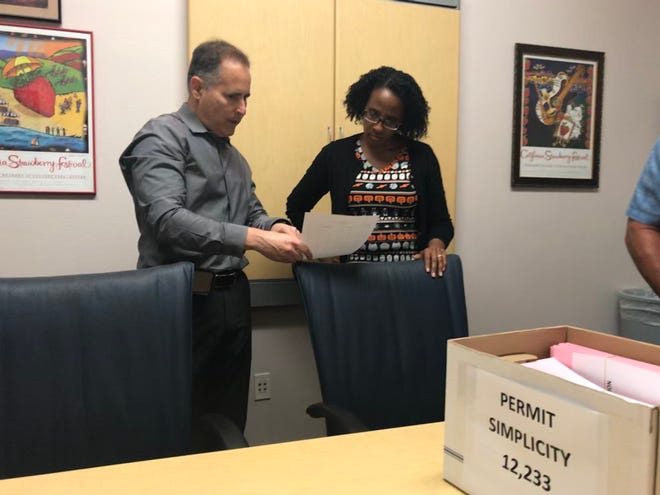 Aaron Starr, left, speaks to Oxnard City Clerk Michelle Ascencion in October when he submitted tens of thousands of signatures in support of five ballot initiatives.
