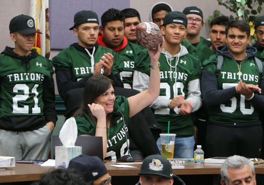 Superintendent Penelope DeLeon holds up a football signed by the entire Pacifica High football team during the Oxnard Union High School District board meeting on Wednesday night.