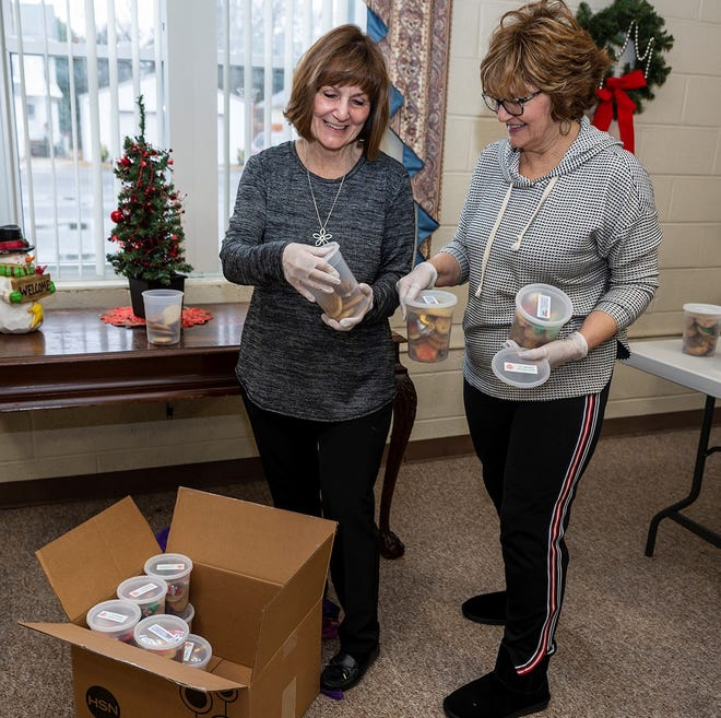 Lisa Fisher (left) and Eda Shannon, co-chairs of the Millville Woman's Club's annual cookie project, pack holiday cookies in containers for residents of senior housing throughout the city. The treats are distributed through the Millville Housing Authority.