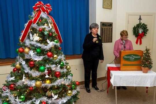 Debbi Permito (left), director of the Millville Woman's Club Chorus, rings a bell as chairperson Barbara Westog reads names of those memorialized in the Millville Woman's Club's annual Tree of Remembrance ceremony held recently at the clubhouse. The project, an annual tradition, benefits the club's high school scholarship. The Chorus and Shades of Blue, the Lakeside Middle School choir, performed at the event.