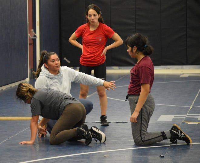 Redwood High varsity girls wrestling coach Rita Ramirez demonstrates a move on Dec. 16, 2019 during practice.