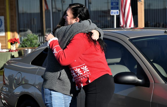 Lisa Colburn, owner of Central Valley Collision Repair, hugs Therese Hutchinson.