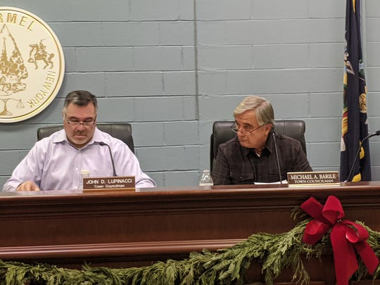Town Board member John Lupinacci, right, reads the board resolution about Board member Mike Barile's illicit sewer connection.