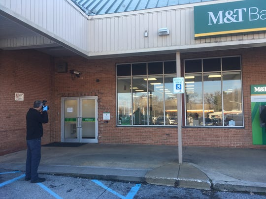 Investigators take photos outside the M&T Bank following a Wednesday robbery.