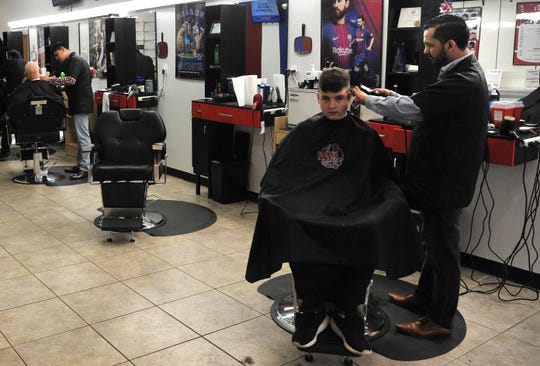 BG's Barber Shop manager, Jose De-La-Mora gives a customer a trim, Thursday afternoon after he and his family moved from New Mexico to Wichita Falls to open their family business located inside of the mall.