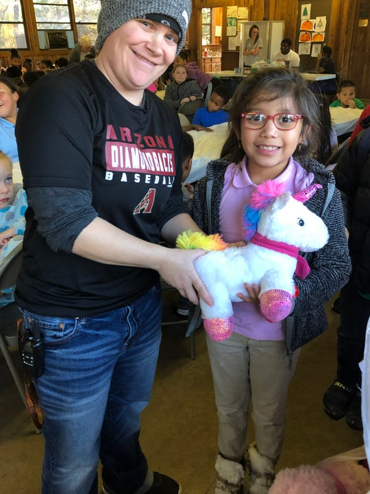 Camp Fire staff member Tiffany Self, left, is seen with Camp Fire member Iliana Perez and her new stuffed animal. Petsmart employees made it possible for every after-school Camp Fire member to receive a stuffed animal for Christmas.