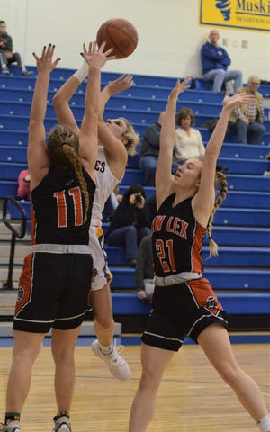 West Muskingum's Hayley Barker goes up for a shot against New Lex's Kim Kellogg (11) and Maggie Skillman (21) in Wednesday's game. The Panthers won 44-39.
