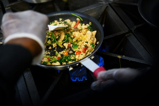 Dwayne Price prepares a tofu scramble in the kitchen at the Flying Biscuit Cafe Friday, Dec. 20, 2019.