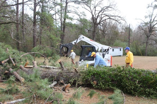 Members of a Southern Baptist Disaster Relief crew work to remove a fallen tree Friday on Holly Moore Drive in Pineville.