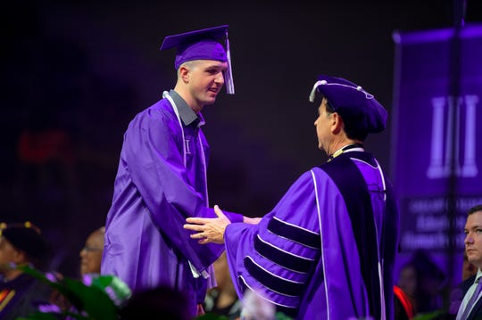 Flint Greer, left, is congratulated by NSU President Dr. Chris Maggio as he walks across the stage at Fall Commencement.