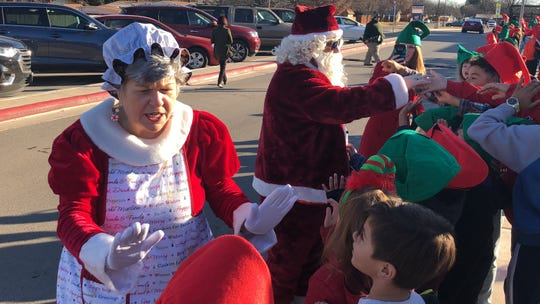 Santa and Mrs. Claus greet Johnston Elementary students Wednesday. The pair participated in the school's Elf Parade after the nearly 700 students met a reading goal for the first semester.