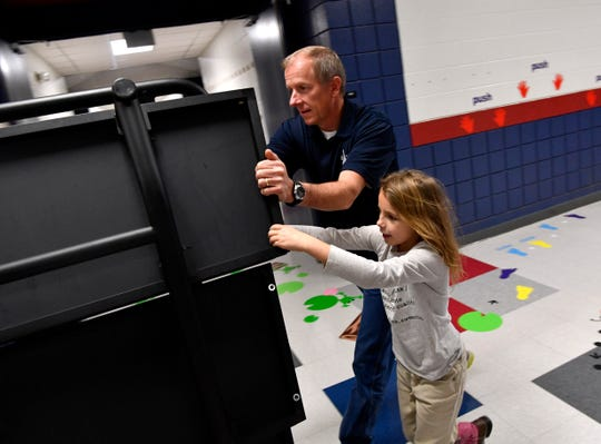 Allie Ward Elementary School Assistant Principal David Hutton is assisted by fifth-grader Grace Flaherty Friday in rolling some fold-up tables down a hallway. Friday was Hutton's last day, he is retiring after almost 30 years in education.