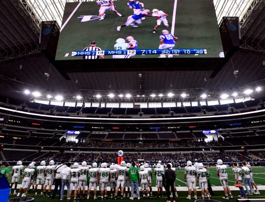 The Hamlin Pied Pipers watch the play action during Thursday's Class 2A Div. II Championship game between them and Mart while overhead the giant video screen at AT&T Stadium shows the same plays to the audience.