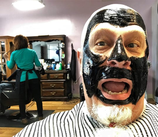 Looking like a character from the wrestling ring, The Masked Marauder, columnist Greg Jaklewicz takes a selfie while stylist Dhipa Hamilton prepares to work on another client while the mask hardens.