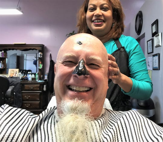 """Stylist Dhipa Hamilton laughs at leaving a dot of mask on the forehead and covering the nose, Coppertone sunscreen style, of columnist Greg Jaklewicz, who got his first """"men's facial"""" recently at her shop. She said his skin felt like that of a baby."""