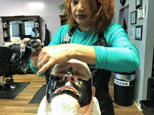 After letting it dry, stylist Dhipa Hamilton begins removing the mask she had applied wet to the face of columnist Greg Jaklewicz. He was relaxing until she started pulling the mask, which got his attention.