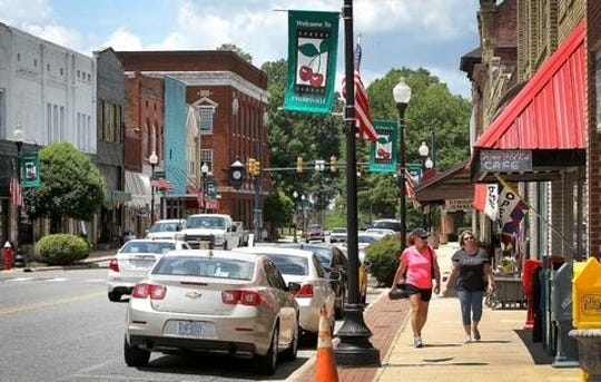 Located in the far western corner of Gaston County, the city of Cherryville has struggled to attract new growth in the past two decades, and its population has grown at a very slow pace. In this photo, people stroll down Main Street in downtown Cherryville on a recent afternoon.