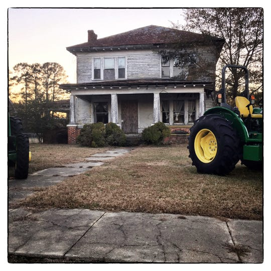 New John Deere tractors sit in the front yard of an aging empty house on Main Street in Seaboard, NC.