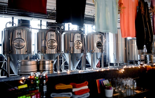 Tanks for brewing beer can be seen from the taproom of the 12 Bones Brewery in Arden.