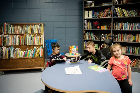 Jacob Peka, 5, Trenton Harmon, 8, and Kylie Rivera, 8, spend time in the new library at Doris Klaussen Developmental Center on Friday, Dec. 20, 2019 in Battle Creek, Mich. The center's former library was a single cart, pictured left in the photograph.