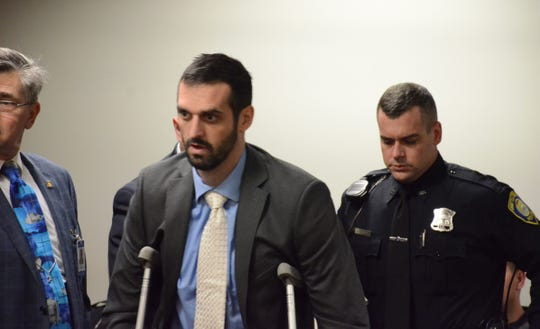 Battle Creek Officer Jeffrey Johnson used a wheelchair and crutches to reach the witness stand on Friday.