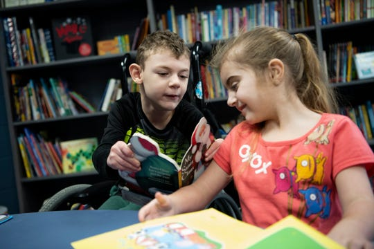 Trenton Harmon, 8, shows Kylie Rivera, 8, a book about Christmas inside the new library at Doris Klaussen Developmental Center on Friday, Dec. 20, 2019 in Battle Creek, Mich. Paige Parrott, 11, learned the school had a new library but no books, so she organized a book drive that brought in 2,500 books.