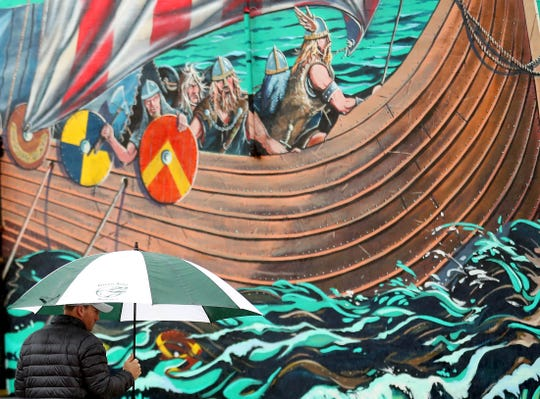 The viking mural looms in the background as an umbrella toting pedestrian crosses the street in downtown Poulsbo on Friday.
