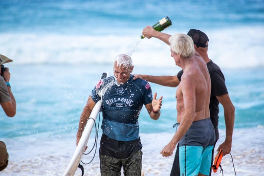 Cocoa Beach's Kelly Slater gets a celebratory spray after winning his third career Vans Triple Crown of Surfing title at Oahu, Hawaii.