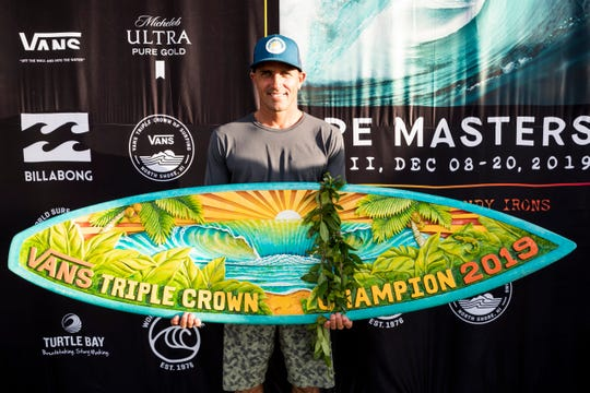Kelly Slater of Cocoa Beach shows off the prize after winning his third Vans Triple Crown of Surfing title at the 2019 Billabong Pipe Masters, 21 years after winning his second at Oahu.