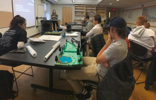 "UVM design students listen as Brooke Tommaney, upper left, describes proposed changes to a Winooski pocket park on Dec. 3, 2019. Foreground: fellow student Ryan Martin's model of a ""bark-park"" (canine recreation area) proposed for a traffic cloverleaf near Ethan Allen Homestead Park in Burlington. The presentations were part of a ""Finding Lost Space"" project for David Raphael's landscape architecture class."