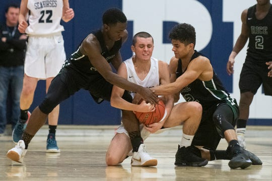 Rice's Heath Walker (12) and Sharif Sharif (10) battle for the ball with Burlington's Jackson Sevakian (5) during the boys basketball game between the Rice Green Knights and the Burlington Seahorses and Burlington High School on Thursday night December 19, 2019 in Burlington, Vermont.