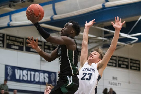 Rice's Michel Ndayishimiye (2) leaps for a layup past Burlington's Ryan Murray (23) during the boys basketball game between the Rice Green Knights and the Burlington Seahorses and Burlington High School on Thursday night December 19, 2019 in Burlington, Vermont.