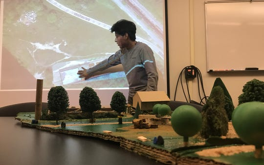 "Andrew Romano, a University of Vermont design student, illustrates how he would transform under-used northern portions of the Burlington waterfront on Dec. 3, 2019. His model is in the foreground. The presentation was part of a ""Finding Lost Space"" project for David Raphael's landscape architecture class."