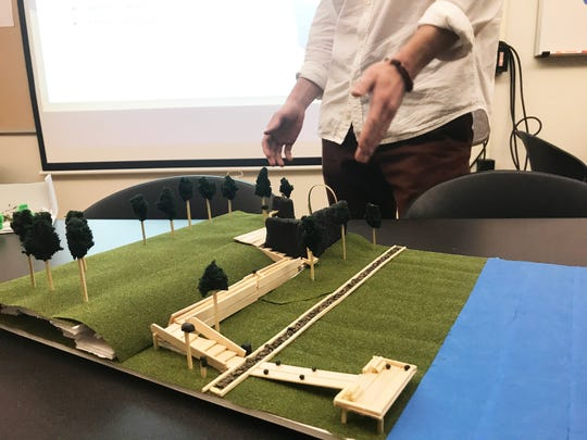 "Andrew Louria, a UVM design student, describes his proposed changes to Winooski's Falls Terrace Park on Dec. 3, 2019. His scale model, which includes a boardwalk to the Winooski River, is in the foreground. The presentation was part of a ""Finding Lost Space"" project for David Raphael's landscape architecture class."