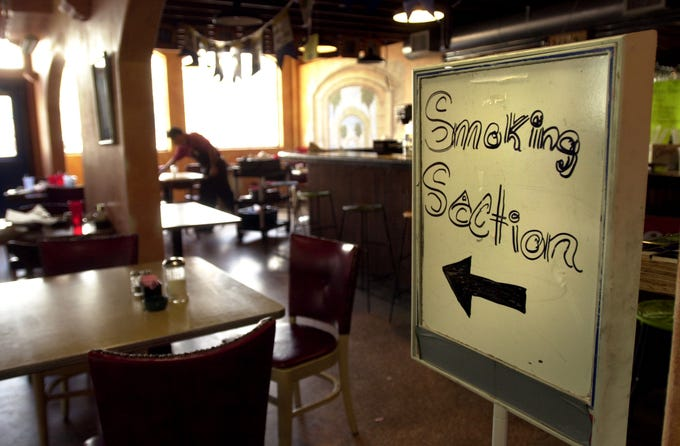 "Mandie Bocanegra and Francisco Navarro clean up the smoking section at La Bahia after lunch June 5, 2001. Bocanegra, who waits tables in the smoking section, says hers is the smallest section in the restaurant. ""Everybody wants to sit in non-smoking,"" she says."