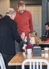Bloomberg high-fives Brenig Lloyd-Prys during his coffee meeting with Mayor Luke Feeney at Paper City Coffee during the presidential candidate's visit to Chillicothe on Dec. 20, 2019.