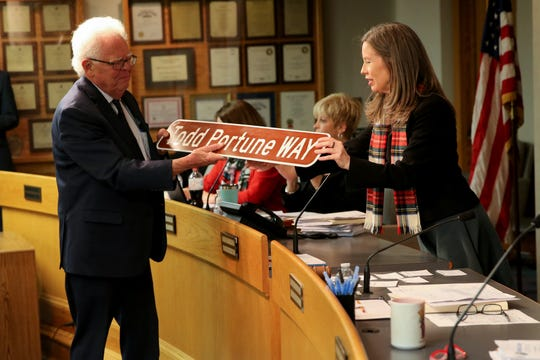 Cincinnati City council member David Mann presents Hamilton County Commission President Denise Driehaus with an honorary road sign, designating a block of East Court Street Todd Portune Way, Thursday, Dec. 19, 2019, during the county commission meeting in Cincinnati.