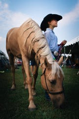 Irelyn Cotton, 9, poses for a portrait with her horse Charlie at the Hamilton County 4-H Community Fair in 2019. Cotton braided the mane of her horse before a competition.