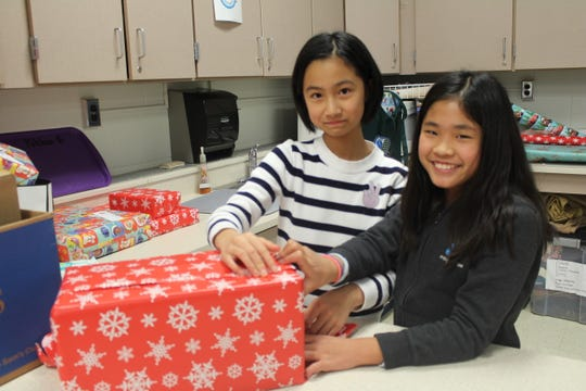 Grade seven students Selina Zhan and Mia Kang work together to wrap more than 50 presents that will be donated to Visions and Pathways.