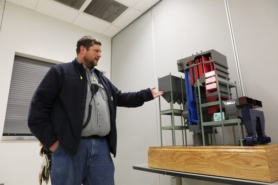 Neil Davis explains the workings of a model of one of the original boilers at AEP's Conesville Generating Station. Davis is one of the plant's employees gathering things from the plant to donate to a museum to help residents remember and learn about the plant. The coal-fired plant will close at the end of the May.