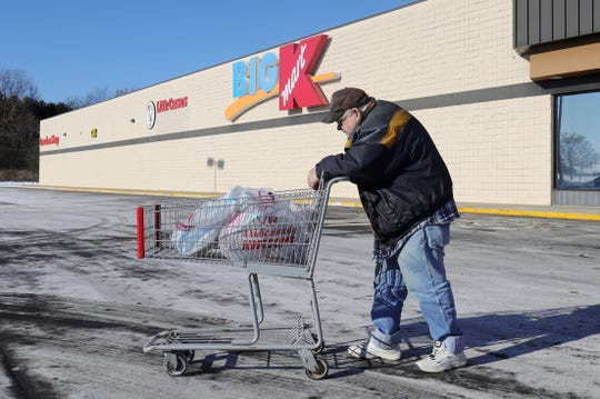 Dewey Minard pushes his cart to his car after shopping at the last standing Kmart store in Marshall Mich. Thursday, December 19, 2019.