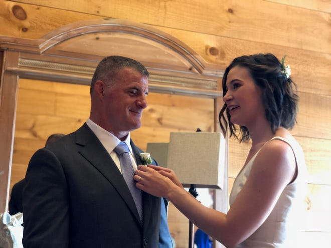 Rebecca Dougherty pins a flower on her father Dale Saran at her wedding last year.