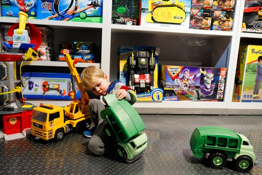 In this Nov. 21, 2019 photo, Maxwell MacIsaac, 2, plays with trucks at Camp toy store in New York.