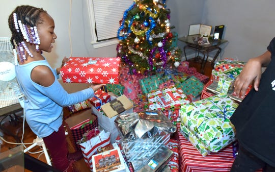 Italy Sanders, 6, reads name tags on the delivered Christmas gifts from Telemus employees, in conjunction with Volunteers of America.