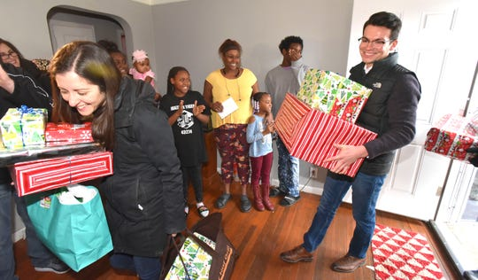 Johannah Schiffer, left, of Huntington Woods, Telemus director of people and places, and financial advisor Thomas Munoz, right, of Troy, deliver gifts to Hermonie Sanders, background-center, 37, and her four children and granddaughter, Friday afternoon.