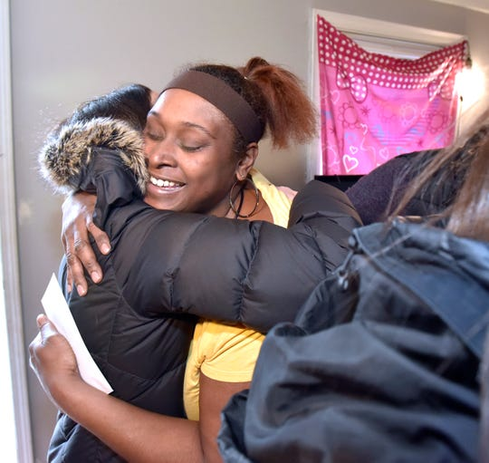 Hermonie Sanders, right, hugs Telemus receptionist Tracy Almassy, of White Lake, after she and co-workers delivered Christmas gifts.