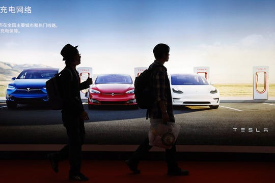 In this April 17, 2019, file photo, attendees walks past advertisement for electric cars from Tesla at the Auto Shanghai 2019 show in Shanghai. Registrations of Tesla vehicles climbed to a five-month high of 5,597 in November, bucking the downturn in the world's biggest electric-vehicle market.
