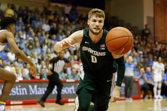 Kyle Ahrens chases down a loose ball during MSU's game against UCLA in the Maui Invitational.
