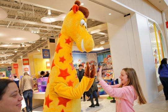 Leah Brackley greets the Toys R Us mascot, Geoffrey, at the new store at a mall in Paramus, N.J., Monday, Dec. 9, 2019. To get shoppers to spend more on toys, stores want them to spend time first.